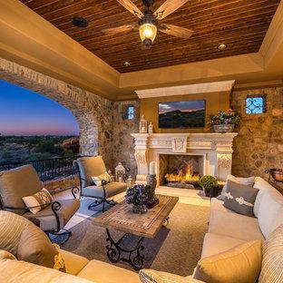 Idee per un ampio patio o portico tradizionale nel cortile laterale con un focolare, pavimentazioni in pietra naturale e un tetto a sbalzo