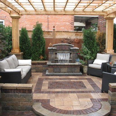 Inspiration for a contemporary patio fountain remodel in Other with a pergola