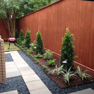 This is an example of a small modern backyard patio in Houston with concrete pavers and no cover.