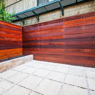 Immagine di un piccolo patio o portico minimalista dietro casa con un giardino in vaso e pavimentazioni in pietra naturale