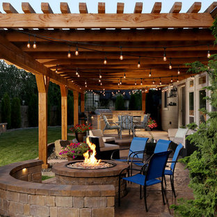 Idées déco pour une terrasse avec une cuisine extérieure arrière montagne de taille moyenne avec du béton estampé et une pergola.