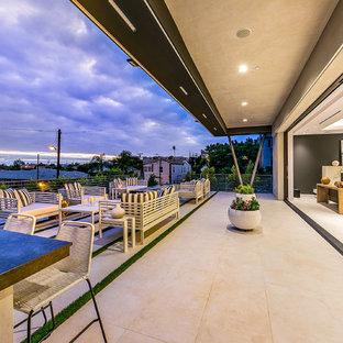 Immagine di un grande patio o portico minimalista dietro casa con un focolare, lastre di cemento e nessuna copertura