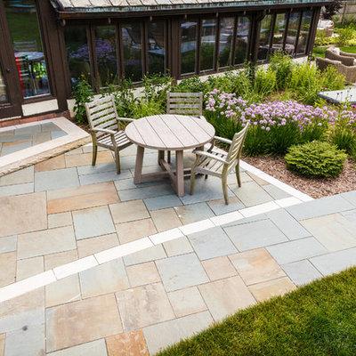 Large elegant backyard stone patio photo in Milwaukee