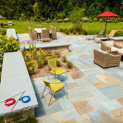 Large elegant backyard stone patio photo in Milwaukee with a fire pit