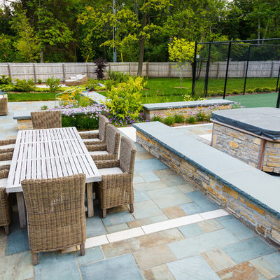 Inspiration for a large timeless backyard stone patio remodel in Milwaukee with a fire pit
