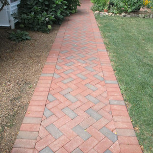Photo of a mid-sized traditional backyard patio in New York with brick pavers.
