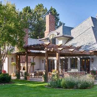 Immagine di un grande patio o portico classico dietro casa con un caminetto, pavimentazioni in pietra naturale e una pergola