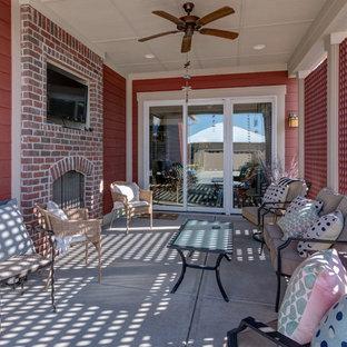 Foto di un piccolo patio o portico stile americano dietro casa con un caminetto, pavimentazioni in cemento e un tetto a sbalzo