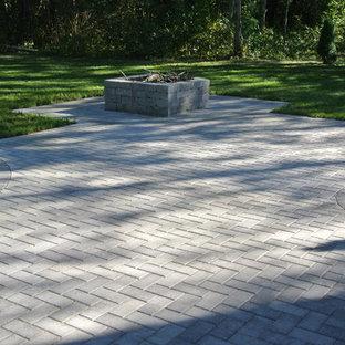 Ispirazione per un patio o portico tradizionale di medie dimensioni e dietro casa con un focolare, pavimentazioni in cemento e nessuna copertura