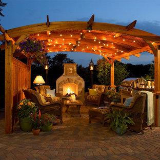 Großer Klassischer Patio hinter dem Haus mit Feuerstelle, Natursteinplatten und Gazebo in Sonstige