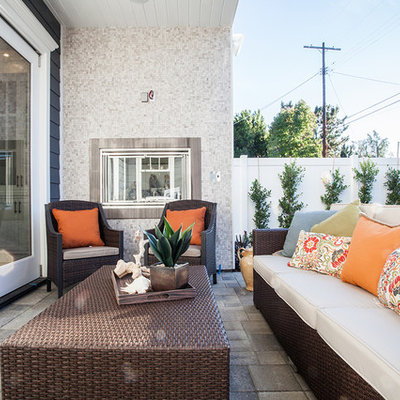 Example of a classic backyard concrete paver patio design in Los Angeles with a roof extension
