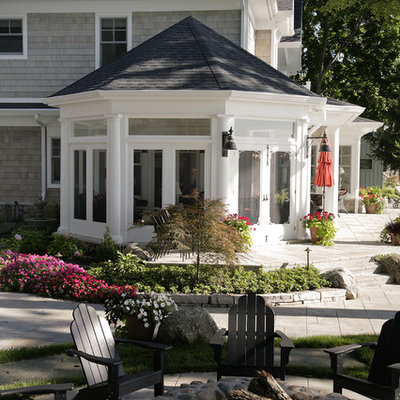 Huge elegant front yard stamped concrete patio photo in Other with a fire pit and a roof extension