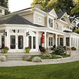 Esempio di un ampio patio o portico tradizionale davanti casa con cemento stampato e un tetto a sbalzo