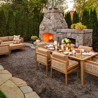 Immagine di un patio o portico chic con un focolare e ghiaia