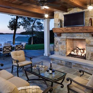 Foto di un patio o portico chic dietro casa e di medie dimensioni con un tetto a sbalzo, pavimentazioni in pietra naturale e un caminetto