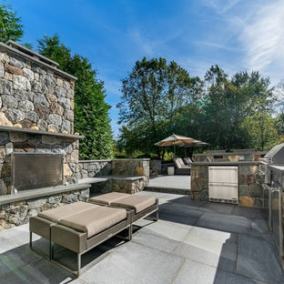 Example of a classic backyard concrete paver patio kitchen design in New York with no cover