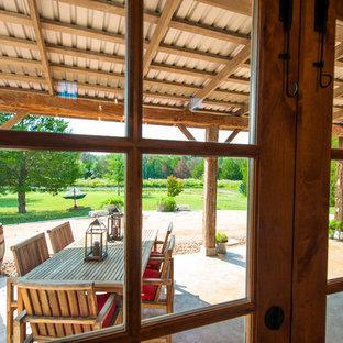 Immagine di un patio o portico tradizionale con un tetto a sbalzo