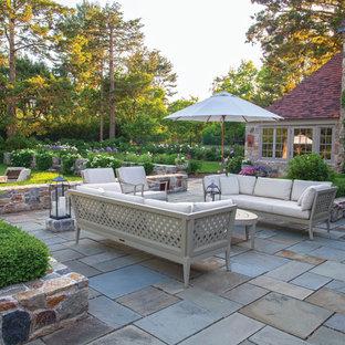 Foto de patio de estilo americano, de tamaño medio, sin cubierta, en patio trasero, con brasero y adoquines de hormigón