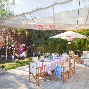 This is an example of a large shabby-chic style back patio in Madrid with an awning.