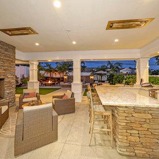 Idee per un ampio patio o portico classico dietro casa con un focolare, graniglia di granito e un tetto a sbalzo