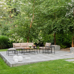 Transitional backyard patio in Boston with natural stone pavers.