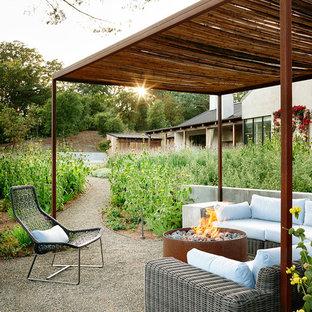 Esempio di un patio o portico country dietro casa con un focolare, ghiaia e un gazebo o capanno