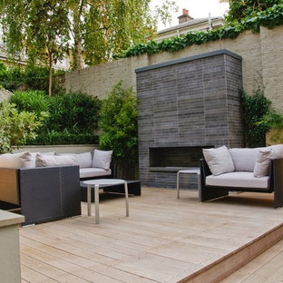 Inspiration for a small contemporary backyard patio in Hertfordshire with decking, no cover and with fireplace.