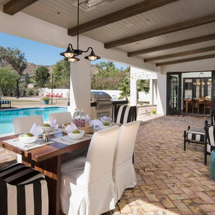 Inspiration for a mediterranean patio in Phoenix with an outdoor kitchen, brick paving and a roof extension.