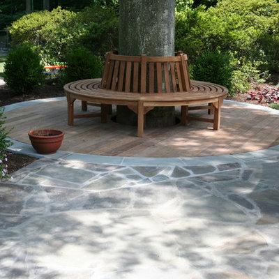 Example of a trendy backyard stone patio design in DC Metro