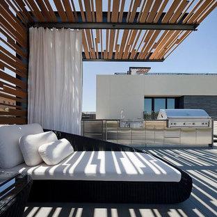 Ejemplo de patio minimalista, extra grande, en patio trasero, con cocina exterior, adoquines de hormigón y pérgola