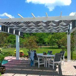 Patio - traditional backyard patio idea in New York with a pergola