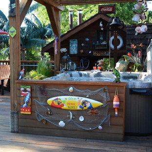 Esempio di un patio o portico tropicale di medie dimensioni e dietro casa con una pergola, un focolare e ghiaia