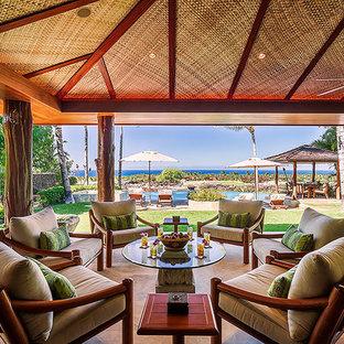 Ispirazione per un patio o portico tropicale dietro casa con graniglia di granito e un tetto a sbalzo