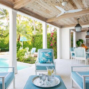 Esempio di un patio o portico tropicale con un tetto a sbalzo