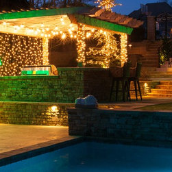Tropical Oasis with Lighted Palm Trees and Patio Lights - Let your guests see at night when they venture into your backyard when the weather gets warmer. Patio lights, icicle lights and lighted palm trees guide the way for anyone who stumbles into your outdoor abode while adding decorative life to the space.