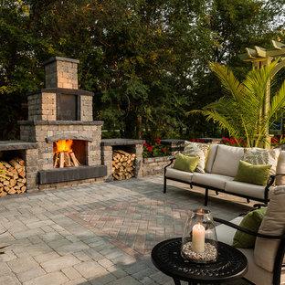 Immagine di un grande patio o portico tropicale dietro casa con nessuna copertura, pavimentazioni in mattoni e un caminetto