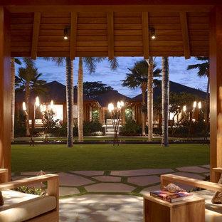 Diseño de patio tropical, en anexo de casas, con adoquines de piedra natural