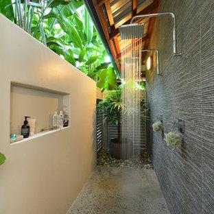 Esempio di un piccolo patio o portico tropicale dietro casa con lastre di cemento e un tetto a sbalzo
