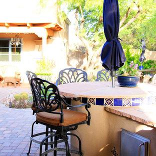 Idee per un patio o portico mediterraneo di medie dimensioni e dietro casa con pavimentazioni in mattoni e un tetto a sbalzo