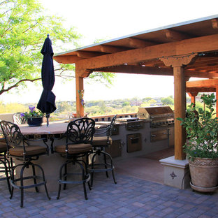 Inspiration for a mid-sized mediterranean backyard brick patio kitchen remodel in Phoenix with a roof extension