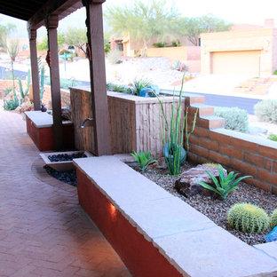 Immagine di un patio o portico american style di medie dimensioni e dietro casa con pavimentazioni in mattoni, fontane e un tetto a sbalzo