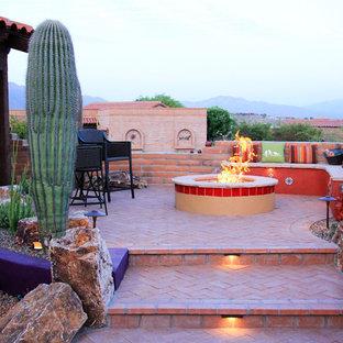 Cette photo montre une terrasse arrière sud-ouest américain de taille moyenne avec un foyer extérieur, des pavés en brique et aucune couverture.