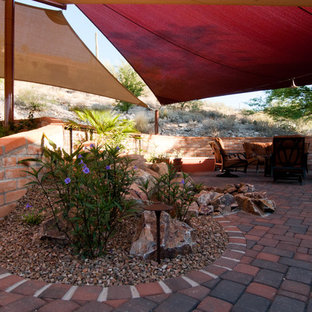 Inspiration for a medium sized back patio in Phoenix with brick paving and an awning.