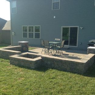 Immagine di un patio o portico chic di medie dimensioni e dietro casa con un focolare e pavimentazioni in mattoni