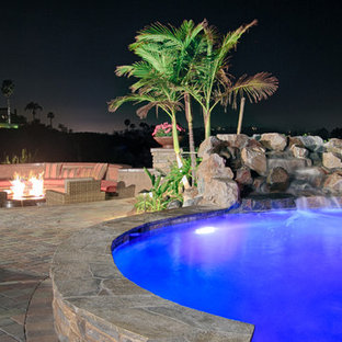 Inspiration for a large transitional backyard patio in San Diego with a water feature, concrete pavers and a roof extension.