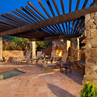 Idee per un patio o portico mediterraneo di medie dimensioni e dietro casa con un focolare, lastre di cemento e un gazebo o capanno