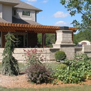 Foto på en stor medelhavsstil uteplats på baksidan av huset, med en öppen spis och en pergola