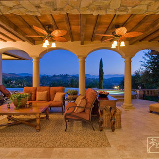 Large tuscan backyard tile patio photo in Los Angeles with a fire pit and a roof extension