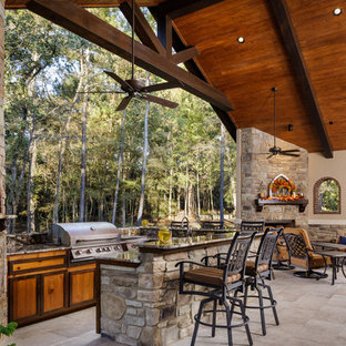 This is an example of a large mediterranean back patio in Houston with tiled flooring, a roof extension and an outdoor kitchen.