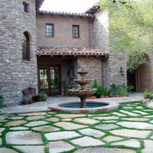 This is an example of an expansive mediterranean courtyard patio in San Diego with a water feature, natural stone pavers and no cover.